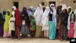 FILE - In this Aug. 31, 2012, photo, women and girls, wearing veils to comply with the dictates of Islamist group Ansar Dine, attend a public lashing in Timbuktu, Mali.