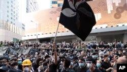 Một người biểu tình vẫy lá cờ màu phiên bản màu đen của Hong Kong bên ngoài trụ sở cảnh sát ở Hong Kong hôm 21/6. Hơn 1.000 người đã phong tỏa trụ sở cảnh sát Hong Kong trong khi những người khác tràn ra các đường phố chính để yêu cầu chính phủ rút lại dự luật dẫn độ.
