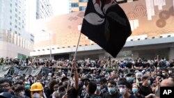 香港抗议者2019年6月21日在香港警察总部外挥舞染成黑色的香港特区旗帜抗议警方暴力。