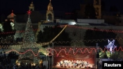 Musicians perform on stage in Manger Square, outside the Church of the Nativity, the site revered as the birthplace of Jesus, on Christmas eve in the West Bank town of Bethlehem, December 24, 2012.