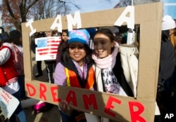 FILE - Demonstrators hold a sign during an immigration rally in support of the Deferred Action for Childhood Arrivals (DACA), on Capitol Hill in Washington, Dec. 6, 2017.