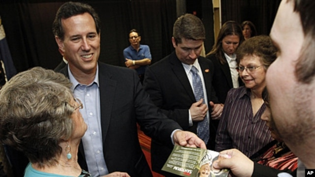 Republican presidential candidate former Pennsylvania Sen. Rick Santorum hands back an autographed campaign flyer at a rally in Shreveport, Louisiana, March 23, 2012.
