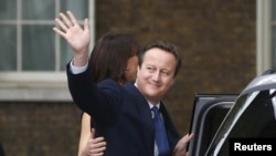 Britain's outgoing Prime Minister, David Cameron with his wife, Samantha, waves in front of number 10 Downing Street, on his last day in office as Prime Minister, in central London, Britain, July 13, 2016.