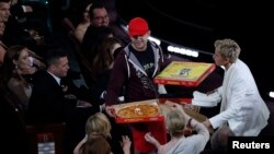 Show host Ellen DeGeneres gives out pizza at the Academy Awards.