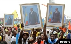 FILE - Supporters of Congolese President Joseph Kabila carry his photographs during a pro-government rally in the Democratic Republic of Congo's capital Kinshasa, July 29, 2016.