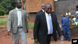 FILE: Elton Mangoma, centre, former Zimbabwe's Minster of Energy and Power Development outside the magistrates courts, accompanied by two unidentified police detectives in Harare, Friday, March, 11, 2011.