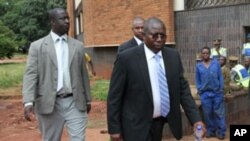 Elton Mangoma, centre, Zimbabwe's Minster of Energy and Power Development outside the magistrates courts, accompanied by two unidentified police detectives in Harare, Friday, March, 11, 2011. Morgan Tsvangirai, Prime Minster of Zimbabwe, castigated the ar