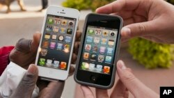 FILE - Noah Meloccaro, right, compares his older iPhone 4s to the new iPhone 5 held by Both Gatwech, outside the Apple Store in Omaha, Neb., Friday, Sept. 21, 2012 on the first day the iPhone 5 was offered for sale.
