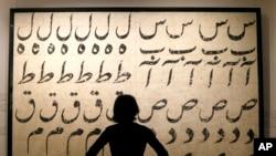 یک کارمند ساتبی به نقاشی فرهاد مشیری، نقاش ایرانی نگاه می کند.