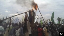 Muslims burn a US flag and a portrait of U.S. President Barrack Obama following a protest in Kano, Nigeria, September 22, 2012.