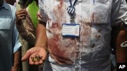 Pokiston xavfsizlik xizmati xodimi xuruj joyidan topilgan dalillarni namoyish qilmoqda. Karachi, 13-may 2015-yil