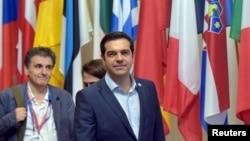 Perdana Menteri Yunani Alexis Tsipras (tengah) dan Menteri Keuangan Yunani Euclid Tsakalotos meninggalkan KTT pemimpin zona euro di Brussels, Belgia (13/7).