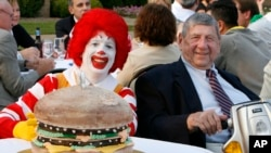 In this Aug. 21, 2008 file photo Big Mac creator Jim Delligatti, right, poses with a Big Mac birthday cake and Ronald McDonald at his 90th birthday party in Canonsburg, Pa.. (AP Photo/Gene J. Puskar/File)