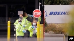 FILE - Workers wearing protective masks stand at an entrance to a Boeing production plant to hand out masks to other workers entering Tuesday, April 21, 2020, in Everett, Wash. (AP Photo/Elaine Thompson)