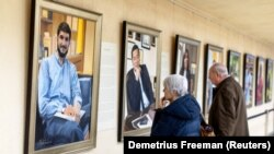 "Visitors examine Betsy Ashton's exhibition, ""Portraits of Immigrants"""