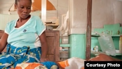 Antho watches over her son Kaba, two, who is being treated for cerebral malaria at the Tshilundu Referral Hospital in Kasai Oriental Province, DRC. Kaba is now in a coma. Antho is nine months pregnant. This is her eighth pregnancy; she had two miscarriages and a daughter who died of malaria aged just eleven months because the clinic they took her to was closed when they arrived. This is not unusual: many local clinics in DRC are under equipped and under staffed. (Credit: Ivy Lahon / Save the Children)