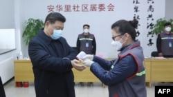 中国国家主席习近平戴着口罩视察北京安华里小区时一名防疫人员检测他的体温。(2020年2月10日)