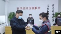 中國國家主席習近平戴著口罩視察北京安華里小區時一名防疫人員檢測他的體溫。(2020年2月10日)