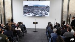 Invitados esperan el inicio de la ceremonia de inauguración de un piso hecho con armas derretidas en Bogotá, Colombia, el martes 31 de julio de 2018.