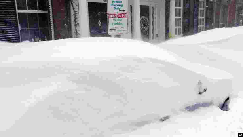 La neige recouvre véhicules garés à Beacon Hill à Boston, dimanche 15 février, 2015. Un avertissement de blizzard était en vigueur pour les communautés côtières de Rhode Island dans le Maine.