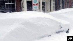 Mobil-mobil di kota Boston tertimbun salju yang turun sejak Minggu (15/2).