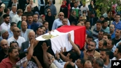 FILE - People carry the coffin, covered with the an Egyptian flag, of police Captain Ahmed Fayez at Al-Hosary mosque in Cairo, Oct. 21, 2017. Fayez was killed Oct. 20 in a gunbattle with militants in al-Wahat al-Bahriya area in Giza province, about 135 kilometers (84 miles) southwest of Cairo.