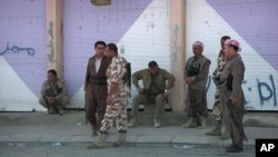 An image from a Sept. 8, 2014 video shows Kurdish Peshmerga standing on a street in Gwer, a northern Iraq town that was recently freed from Islamic State control.