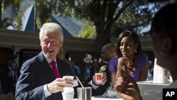Former U.S. President and U.N. special envoy to Haiti, Bill Clinton, left, holds a coffee before the opening ceremony of an investor conference at the Karibe hotel in Port-au-Prince, Haiti, November 29, 2011.
