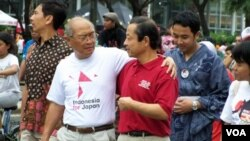 Penggagas acara 'Indonesia for Japan,' Kuntoro Mangkusubroto (kaos putih), dan Dubes Jepang untuk RI, Kojiro Shiojiri (kaos merah) dalam acara yang berlangsung di kawasan Thamrin, Jakarta, Minggu (27/3).
