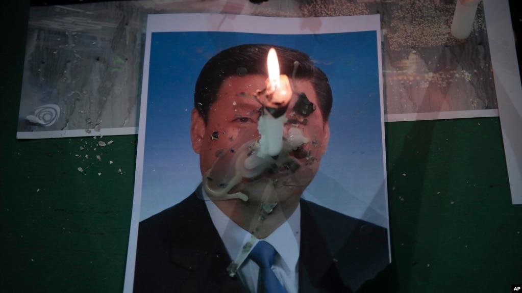 2020年6月4日,星期四,在香港铜锣湾维多利亚公园为1989年天安门广场大屠杀遇难者举行的守夜仪式上,中国国家主席习近平的照片上燃烧着一支蜡烛。(photo:VOA)
