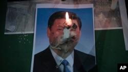 2020年6月4日,星期四,在香港铜锣湾维多利亚公园为1989年天安门广场大屠杀遇难者举行的守夜仪式上,中国国家主席习近平的照片上燃烧着一支蜡烛。