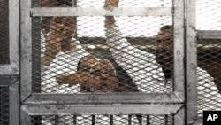 Lãnh đạo Huynh đệ Hồi giáo Mohammed Badie, (dưới cùng, giữa) và nhân vật cao cấp của tổ chức này Salah Soltan, (phải), xuất hiện ở tòa án Cairo, Ai Cập, 1/4/2014.