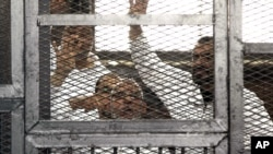 Leader of Egypt's Muslim Brotherhood Mohammed Badie, bottom center, and senior Brotherhood figure Salah Soltan, right, gesture during an appearance at a courtroom in Cairo, Egypt, April 1, 2014.