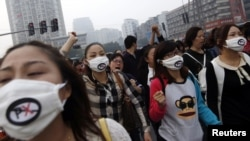 People shout slogans as they march during a protest against plans to expand a petrochemical plant in Ningbo, Zhejiang province, October 28, 2012.