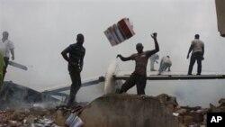 Wananchi wakirusha mabaki ya ndege ya Dana Airlines , katika eneo la makazi ya watu kaskazini mwa uwanja wa ndege wa kimataifa wa Murtala Muhammed Jumapili Juni 3, 2012.