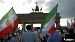 FILE - Activists hold flags during a demonstration against executions in Iran in Berlin, Germany, Sept. 3, 2016.