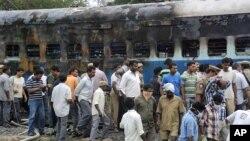 Trabajadores del ferrocarril y autoridades inspeccionan el vagón del tren que se incendió en la India, causando la muerte a al menos 47 personas.