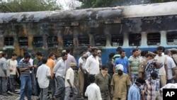 鐵路工作人員和有關官員星期一在離印度南部的海得拉巴大約500公里處檢查一節燒焦的車廂