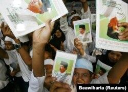 Ilustrasi. Sekelompok siswa Indonesia memegang foto kandidat presiden Susilo Bambang Yudhoyono di sebuah sekolah Islam di Bandung, 27 Agustus 2004. (Foto: Reuters/Beawiharta)