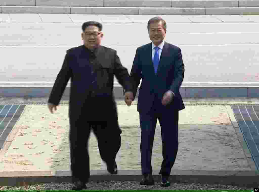 In this image taken from video provided by Korea Broadcasting System, April 27, 2018, North Korean leader Kim Jong Un, left, crosses the border into South Korea, along with South Korean President Moon Jae-in for their historic face-to-face talks, in Panmu