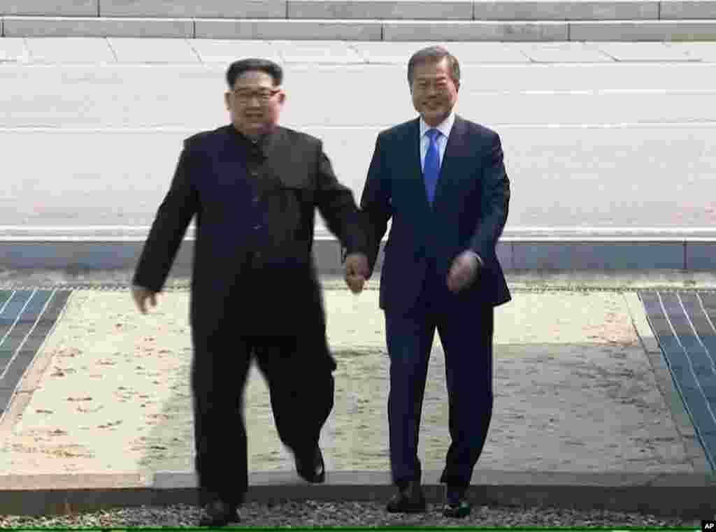 ក្នុងរូបភាពដែលថតចេញពីវីដេអូផ្តល់ឲ្យដោយប្រព័ន្ធផ្សព្វផ្សាយរបស់កូរ៉េ នៅថ្ងៃទី ២៧ ខែមេសា ឆ្នាំ២០១៨ បង្ហាញពីមេដឹកនាំកូរ៉េខាងជើង លោក Kim Jong Un ឆ្លងព្រំដែនចូលប្រទេសកូរ៉េខាងត្បូងជាមួយនឹងប្រធានាធិបតីកូរ៉េខាងត្បូងលោកMoon Jae-in សម្រាប់ការចរចាផ្ទាល់មុខជាប្រវត្តិសាស្រ្តរបស់ពួកអស់លោក នៅក្នុងភូមិ Panmunjom។