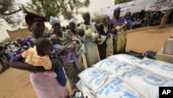 Women wait to receive baby food in Koleram, southern Niger, during the launch of a UN-backed feeding operation aimed at fighting malnutrition among young children, 28 Apr 2010