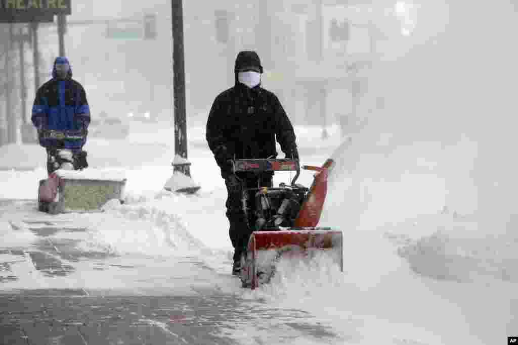 Para pekerja mencoba membersihkan salju dari trotoar dalam badai salju di Boston (27/1). (AP/Steven Senne)
