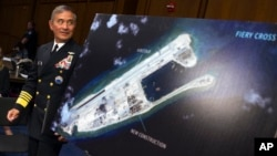 美国海军上将哈里斯走过一张照片,照片显示中国在永暑礁上施工(2015年9月17日)