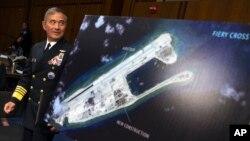 Tư lệnh Bộ Chỉ huy Hoa Kỳ ở Thái Bình Dương, Đô đốc Harry Harris, đứng bên bức ảnh vệ tinh cho thấy hòn đảo nhân tạo mà Trung Quốc xây trên bãi đá Chữ thập, tháng Chín năm 2015.