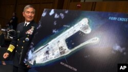 FILE - Adm. Harry B. Harris, Jr., US Navy Commander, U.S. Pacific Command walks past a photograph showing an island that China is building on the Fiery Cross Reef in the South China Sea, as the prepares to testify on Capitol Hill in Washington, Sept. 17, 2015,