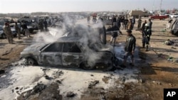 A destroyed car smolders after a bombing in Karbala, 80 kilometers (50 miles) south of Baghdad, Iraq, 20 Jan 2011