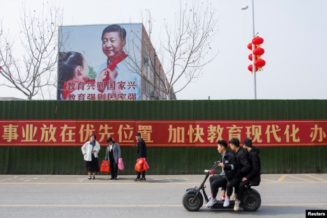 Men ride a scooter past a poster showing Chinese President Xi Jinping on the side of a school building in Henan province, China February 22, 2019.