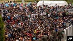 Para migran antri menunggu bis setibanya di perbatasan antara Austria dan Hungaria dekat Heiligenkreuz, 180 kilometer selatan Wina, Austria (19/9).