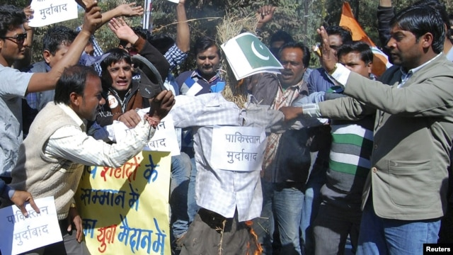 Activists of the youth wing of India's ruling Congress party shout slogans as they beat and burn an effigy depicting Pakistan during a protest in the central Indian city of Bhopal, January 9, 2013.